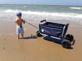 Beachtrekker Bollerwagen blau am Strand mit Jungen